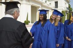 Graduados en la línea para sacudir la mano del decano fuera de la universidad Foto de archivo libre de regalías