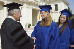 Graduados en la línea para sacudir la mano del decano fuera de la vista lateral de la universidad Fotografía de archivo libre de regalías