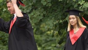 Graduados engraçados nos vestidos acadêmicos que dançam e que cantam no parque perto da universidade filme