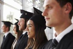 Graduados felizes nos almofarizes e os vestidos, o principal e os ombros imagem de stock royalty free