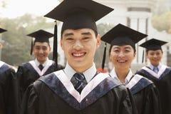 Graduados jovenes en casquillo y vestido Imagenes de archivo
