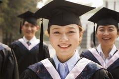 Graduados jovenes en casquillo y vestido Fotos de archivo libres de regalías