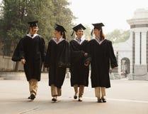 Graduados jovenes que caminan a través de campus Fotos de archivo libres de regalías