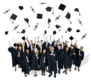 Graduados que lanzan sus sombreros de la graduación Foto de archivo libre de regalías