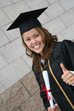Graduate. A pretty graduate celebrating her success with diploma Royalty Free Stock Photography