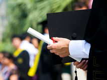 Graduate. Graduating student holding their diploma proudly royalty free stock image