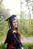 Graduate. Student in cap and gown outside for graduation stock photos