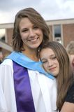 Graduate. A young woman gets a hug from her sister after graduating from school Royalty Free Stock Photo