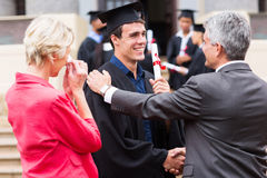 Graduate being congratulated. Handsome male graduate being congratulated by his father at graduation ceremony Royalty Free Stock Images
