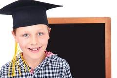 Graduate boy in cap with blackboard in background Stock Photo