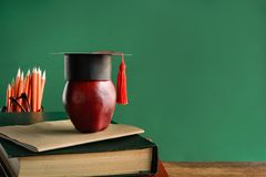 Graduate cap and apple on old book at library green wall backgro Stock Photography