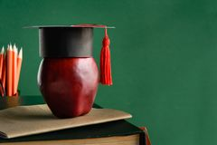 Graduate cap and apple on old book at library green wall backgro Royalty Free Stock Images