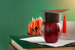 Graduate cap and apple on old book at library green wall backgro Stock Photo