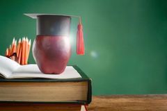 Graduate cap and apple on old book at library green wall backgro Royalty Free Stock Photography