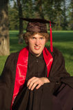 Graduate in Cap and Gown. A young male student in cap and gown, park like setting Stock Photography