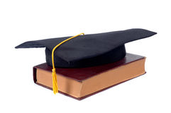 Graduate cap and old book. Isolated on white background Royalty Free Stock Images