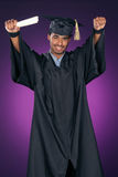 Graduate celebrating. Young man with his arms raised is celebrating his achievement as he graduate's Royalty Free Stock Images