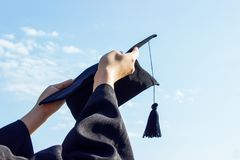 Graduate celebrating with cap in her hand,feeling so proud and happiness in Commencement day.  Royalty Free Stock Images