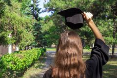 Graduate celebrating with a cap in her hand,feeling so proud and happy in graduation day.  Royalty Free Stock Image