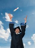 Graduate in cloak throwing diploma Royalty Free Stock Photo