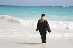 Graduate contemplating future. Blonde female graduate contemplating future while walking on the beach Stock Photos