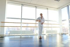 Dance school graduate making body movements. Graduate of dance school moves in white suit. Happy guy raving at gym. Concept of promotion to start dancing career Stock Photos
