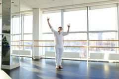 Dance school graduate making body movements. Graduate of dance school moves in white suit. Happy guy raving at gym. Concept of promotion to start dancing career Stock Photography