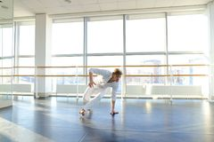 Dance school graduate making body movements. Graduate of dance school moves in white suit. Happy guy raving at gym. Concept of promotion to start dancing career Royalty Free Stock Image