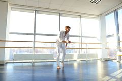 Dance school graduate making body movements. Graduate of dance school moves in white suit. Happy guy raving at gym. Concept of promotion to start dancing career Royalty Free Stock Images