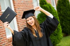 Graduate: Female Graduate Cheering WIth Diploma. Pretty Asian American woman in black graduatation cap and gown, outdoors Stock Images