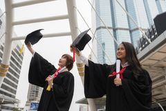 Graduate female students in Commencement day. Asian beautiful graduated female students with black graduation gowns hold diploma and raise cap hats with modern Royalty Free Stock Photo