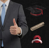 Graduate giving thumbs up. Businessman graduate giving thumbs up sign Stock Image