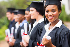 Graduate at graduation. Pretty african female college graduate at graduation with classmates Royalty Free Stock Image