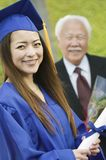 Graduate with Grandfather behind outside portrait Royalty Free Stock Photos