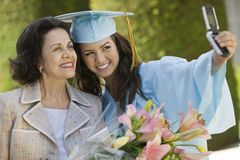 Graduate and Grandmother Taking Picture with Cell Royalty Free Stock Photos