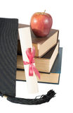 Graduate hat, books, apple and scroll Royalty Free Stock Photography