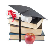 Graduate hat, books, apple and scroll Stock Photos