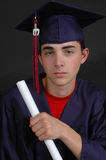 Graduate from High School. Senior High School Boy in his cap in gown posing for Senior Portraits stock photos