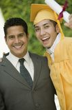 Graduate hoisting diploma with arm around father outside portrait Stock Photography