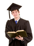 Graduate holding a book. A smiling university graduate holding a book, isolated on white Royalty Free Stock Photo