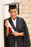 Graduate holding diploma Stock Image