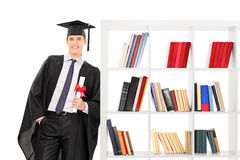 Graduate holding diploma and leaning on bookshelf. Isolated on white background Royalty Free Stock Images