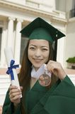 Graduate holding diploma and medal Stock Images