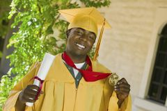Graduate holding diploma and medal outside Stock Photo