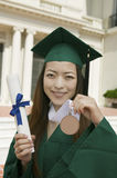 Graduate Holding Diploma And Medal Outside University Stock Image