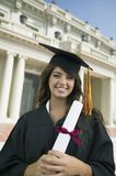 Graduate holding diploma outside university portrait Stock Images