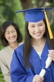 Graduate Holding Diploma With Mother Behind Outside Portrait Royalty Free Stock Images