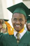 Graduate Holding Medal outside Stock Photo