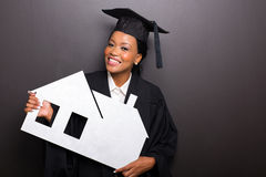 Graduate holding paper house Stock Image