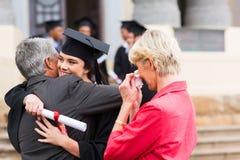 Graduate hugging father. Beautiful young female graduate hugging her father at graduation Stock Photos